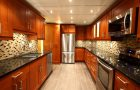 Newly renovated modern luxury kitchen with stainless steel appliances, mosaic backsplash, black galaxy granite counter tops and medium-brown cabinetry
